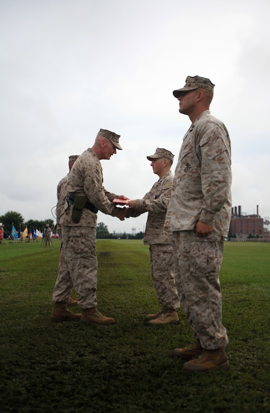 Philadelphia native, Cpl. Jason M. Hassinger (center right), receives the Silver Star Medal from Maj. Gen. John A. Toolan, the outgoing commanding general of 2nd Marine Division during the 2nd Marine Division change of command ceremony Aug. 23 aboard Camp Lejeune. Hassinger received the Silver Star for his actions during an ambushed patrol in Marjah, Helmand province, Afghanistan, in which he led his section through intense fire to rescue a group of fellow Marines pinned down by the enemy.  Hassinger was shot four times during the incident but continued to fight until the enemy retreated.  The Silver Star is the third-highest award a U.S. service member can receive for valor in combat.