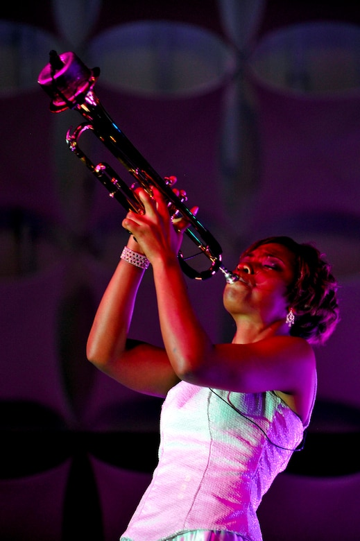 """DENVER -- Airman 1st Class Jessica Pitts, 606th Air Control Squadron, Spangdahlem Air Base, Germany, plays a muted trumpet solo at the Wings Over the Rockies Air and Space Museum Aug. 28 for the Tops in Blue """"Listen"""" tour. Performing at a pace of 230 shows in 235 days, Tops in Blue is the Air Force's expeditionary entertainment team that will tour through more than 20 countries this year. (U.S. Air Force photo by Staff Sgt. Kathrine McDowell)"""