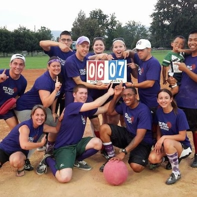 """The AlcoBALLics hold up the final score of their championship victory in the """"Kick Balls, Save Lives"""" Kickball Tournament, Aug. 18, 2012, at Ann Morrison Park in Boise, Idaho. Originally, the tournament's proceeds were to be distributed to various local families affected by cancer, but when one of the victims passed shortly before the tournament, the funds went directly to her relatives instead. (Courtesy photo)"""