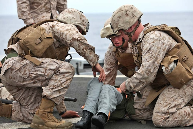 Marines from the 15th Marine Expeditionary Unit treat a simulated casualty during a Combat Life-saving Skills course aboard the USS Rushmore, Aug. 24. The four-day course teaches service members the basic level of Tactical Combat Casualty Care in order to stabilize casualties on the battlefield.
