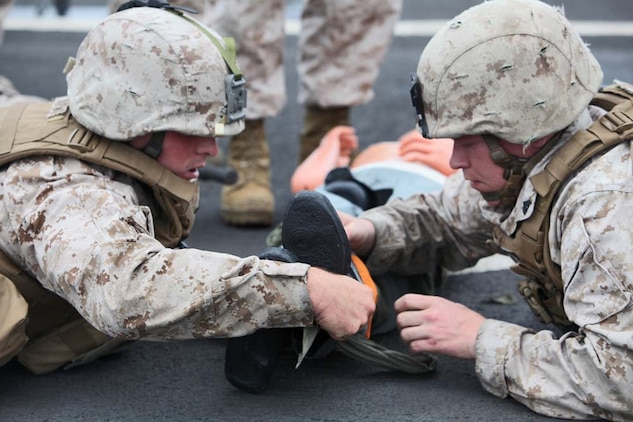 Corporal Michael C. Hartwig (left), motor transportation operator and Cpl. Jacob A. Johnson, motor transportation licensing non-commissioned officer in charge, both with Headquarters and Support Company, Battalion Landing Team 3/5, 15th Marine Expeditionary Unit, apply a splint to a simulated casualty during a Combat Life-saving Skills course aboard the USS Rushmore, Aug. 24. Hartwig ,24, is from Fort Atkinson, Wis,. and Johnson, 25, is from Coalville, Ill.