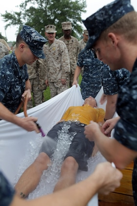 Navy Petty Officer 3rd Class Paul Johnson III is covered in ice and watered as an example victim during the hot weather standard operating procedure training aboard Marine Corps Base Camp Lejeune Aug. 24. Johnson is demonstrating the 'taco' method for cooling an individual suffering from a heat related injury.