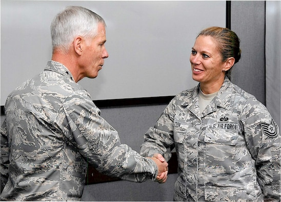 """Gen. William Shelton, Commander, Air Force Space Command, congratulates and """"coins"""" (then technical sergeant) Master Sgt. Sherrie Eden for her Recruiting Service accomplishments.  Eden, an Air Force Reserve line recruiter at the 302nd Airlift Wing at Peterson Air Force Base, Colo. tied for first place in a challenge issued by Shelton. The general asked recruiters to try to find placements for critically manned space operations positions. Eden who placed 48-percent of her recruits in space command during the challenge timeframe, was surprised by the honor. """"I'm just focused on doing my job,"""" said Eden (Courtesy photo)"""