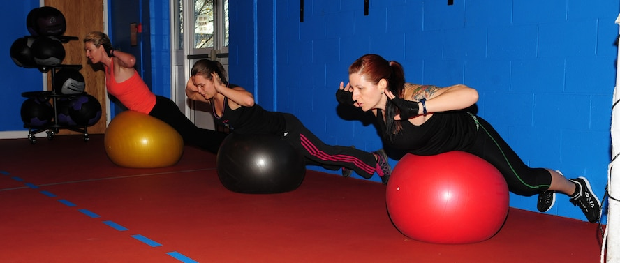 From left, Shana Williams, 100th Security Forces Squadron spouse; Pamela Walker, 321st Special Tactics Squadron spouse; and instructor Brandy Willaman, 48th Component Repair Squadron spouse, perform exercises on fitness balls Nov. 30, 2012, at the North Side Fitness Center, RAF Mildenhall, England. The one-hour class, held Mondays, Wednesdays and Fridays at 9:30 a.m., is one of many offered at the fitness centers on base. (U.S. Air Force photo by Karen Abeyasekere)