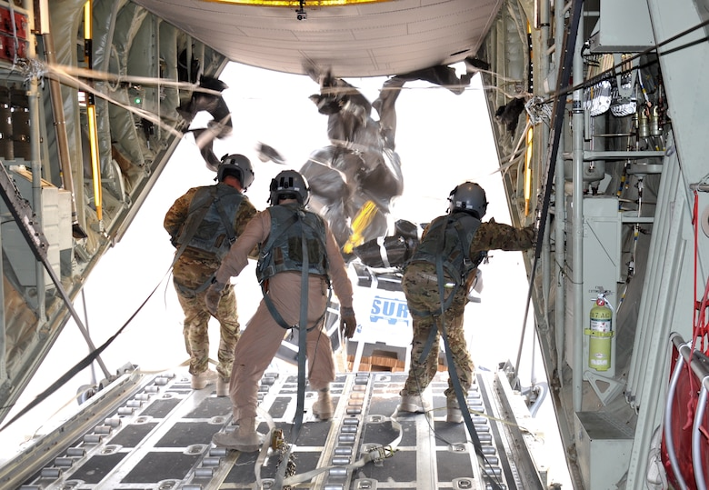 Senior Airman Dan Simonsen, Senior Master Sgt. Steve Martin and Senior Airman Marcus Wright, loadmasters with the 772nd Expeditionary Airlift Squadron, perform a Low Cost, Low Altitude airdrop from the back of a C-130J in southwest Afghanistan Nov. 15. They are deployed from Dyess Air Force Base, Texas. (U.S. Air Force photo/Capt. Tristan Hinderliter)