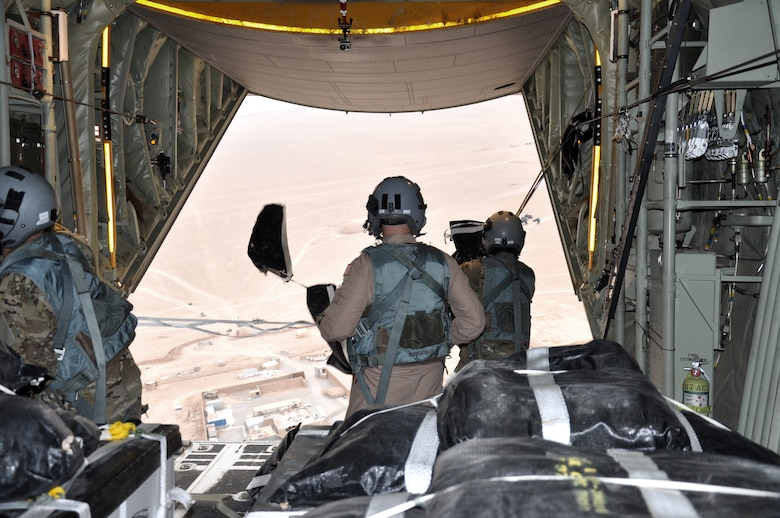 Senior Airman Dan Simonsen, Senior Master Sgt. Steve Martin and Senior Airman Marcus Wright, loadmasters with the 772nd Expeditionary Airlift Squadron, perform a Low Cost Low Altitude airdrop from the back of a C-130J in southwest Afghanistan Nov. 15. They are deployed from Dyess Air Force Base, Texas. (U.S. Air Force photo/Capt. Tristan Hinderliter)