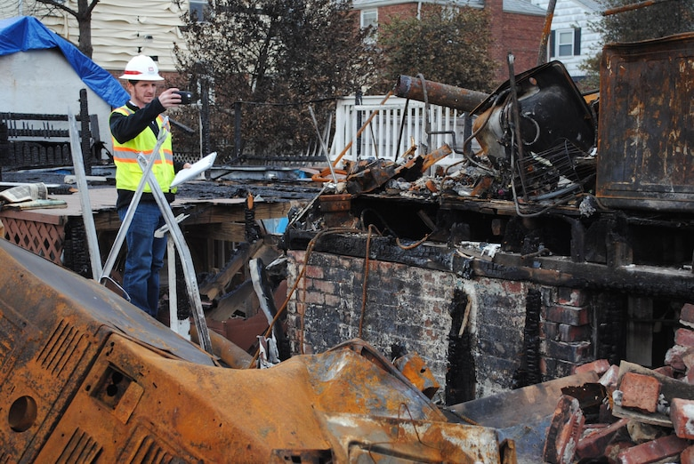 Josh Jimerfield, a debris engineer with the U.S. Army Corps of Engineers New York Recovery Field Office, takes a photo, Nov. 30, of a home burned to the ground on Beach 130th Street in Queens, N.Y. Teams of Army Corps and Federal Emergency Management Agency real estate specialists and field assessors are fanning out into neighborhoods of Queens, Brooklyn and Staten Island to meet homeowners and conduct site assessments.