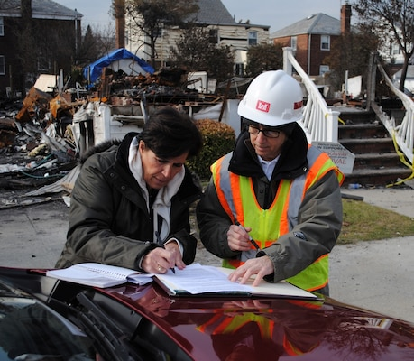 Martha Militano, a resident of the Rockaways in Queens, N.Y., signs a right-of-entry form, Nov. 30, authorizing the U.S. Army Corps of Engineers to remove the remains of her home, pictured behind her, burned to the ground during Hurricane Sandy. Assisting her is Leslie Williams, a real estate specialist with the Army Corps New York Recovery Field Office.