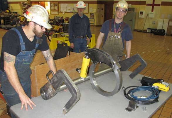 From left, Jake Keizur, Terry Best and Pete Hobart assemble one of two hydraulic wrenches they built for the downstream miter gate on The Dalles navigation lock.