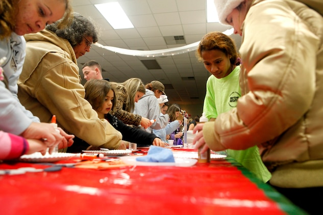 Children and parents create fun arts and crafts during the Tarawa Terrace Community Center Holiday Tree Lighting Ceremony at the Marine Corps Base Camp Lejeune housing community center Dec. 1. The craft table was just one of many different activities of the evening, which also including singing, dancing and a movie.