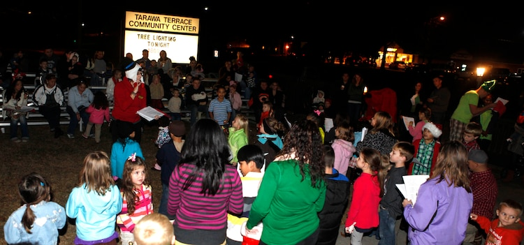 Parents and children sing Christmas carols together during the Tarawa Terrace Community Center Holiday Tree Lighting Ceremony at the Marine Corps Base Camp Lejeune housing community center Dec. 1. The event was a big hit, as an estimated 360 people were in attendance for the holiday festivities.