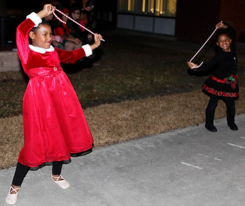 Two young dancers perform with candy-cane props during the Tarawa Terrace Community Center Holiday Tree Lighting Ceremony at the Marine Corps Base Camp Lejeune housing community center Dec. 1. Young entertainers from the community center's Dance With Me Academy provided pleasant diversions from the winter chill for the event's patrons throughout the evening.