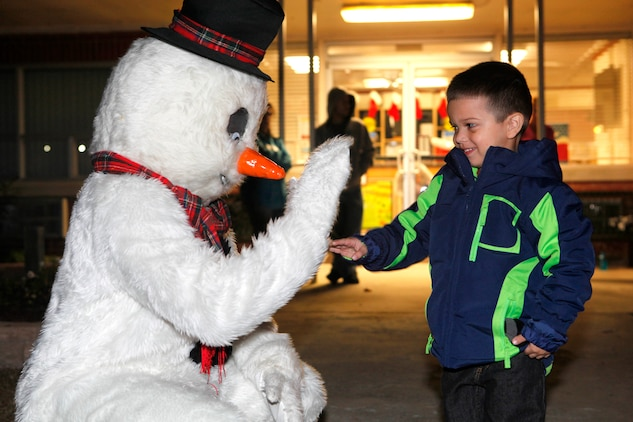 A boy shakes hands with Frosty the Snowman during the Tarawa Terrace Community Center Holiday Tree Lighting Ceremony at the Marine Corps Base Camp Lejeune housing community center Dec. 1. Frosty was one of the many lovable Christmas characters present at the tree lighting ceremony.