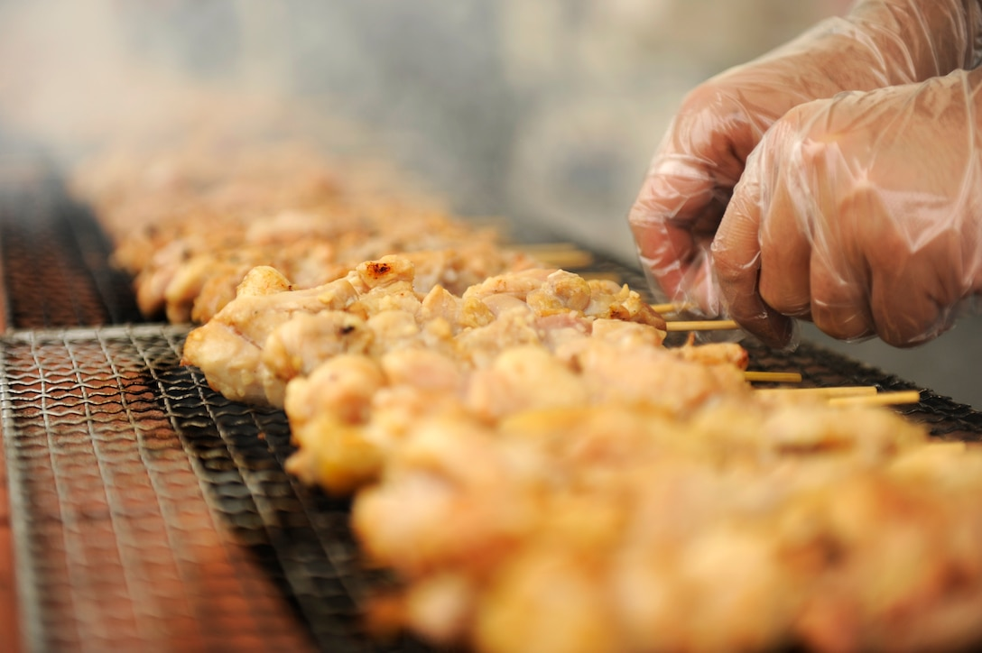 A food vendor prepares garlic chicken skewers at the Tinsel Town holiday festival on Kadena Air Base, Japan, Dec. 1, 2012. The event featured roughly 65 separate vendors, organizations, crafters and volunteers from on- and off-base facilities, promoting a positive relationship with service members and the local community. (U.S. Air Force photo/Senior Airman Maeson L. Elleman)