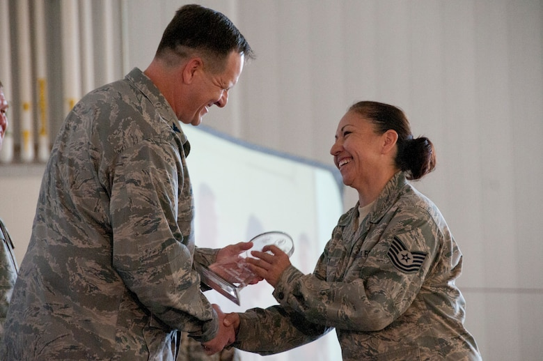 Tech. Sgt. Irasema Perry, contracting officer representative for the 162nd Fighter Wing, is awarded NCO of the Year by Col. Michael McGuire, 162nd Fighter Wing commander, Nov. 3 during the wing's annual awards ceremony. U.S Air Force Photo by Tech. Sgt. Hollie Hansen.