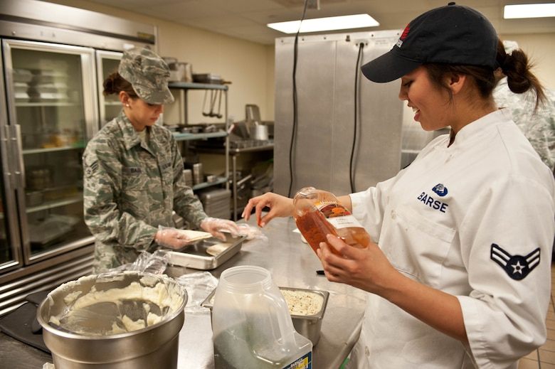 Airman 1st Class Alexandria Barse, and Senior Airman Kelsi Bass, 28th Force Support Squadron flight kitchen cooks, prepare meals for Airmen in the flight kitchen at Ellsworth Air Force Base, S.D., Dec. 4, 2012. The flight kitchen provides Ellsworth personnel with healthy and affordable meal options 24 hours a day. (U.S. Air Force photo by Airman 1st Class Zachary Hada/Released)