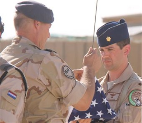 Maj. Dan McGuire, an F-16 exchange pilot who was assigned to the 312th Tactical Fighter Squadron at Volkel Air Base in the Netherlands, prepares to fly a U.S. flag in May 2012 at his base in Mazar-e-Sharif, Afghanistan. McGuire, who participated in the Air Force Personnel Exchange Program, deployed for four months with the Dutch Air Task Force, a detachment of the Royal Netherlands Defense. He flew missions throughout most of Afghanistan supporting the International Security Assistance Force (ISAF) and Operation Enduring Freedom. (Photo by Sgt. Maj. Ruud Medema/Royal Netherlands Air Force)