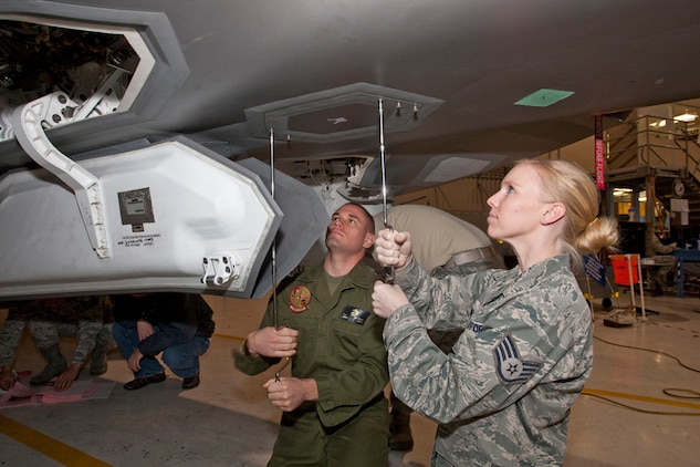 Staff Sgt Brittney Lehr, 412th Aircraft Maintenance Squadron JSF, and Marine Staff Sgt.Thomas Mitsch, Marine Tiltrotor Operational Test and Evaluation Squadron 22, work to remove a panel on an F-35. For more than 18 months, developmental test personnel from the F-35 Integrated Test Force have been responsible for training operational maintainers from the 31st Test and Evaluation Squadron and Marine Tiltrotor Operational Test and Evaluation Squadron 22; the marines who will maintain the F-35B Short Takeoff Vertical Landing variant. Seventy-six personnel have successfully completed the program with 15 maintainers currently participating.
