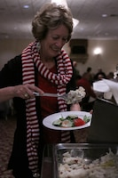 Carolyn Brown, a 5 year volunteer with the Navy-Marine Corps Relief Society, helps herself to mashed potatoes during the NMCRS luncheon at the Pacific Views Event Center here Dec. 4. The Massachusetts native was awarded for her time spent volunteering at the base thrift shop.