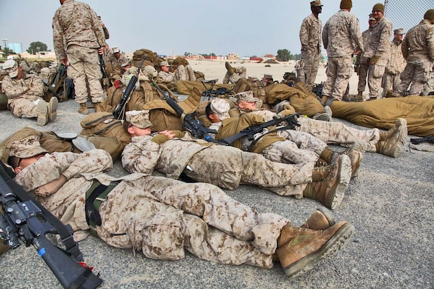 Marines assigned to the 15th Marine Expeditionary Unit catch some rest as they wait for a Landing Craft Air Cushion to transport them and their cargo from Camp Patriot, Kuwait, to the USS Rushmore on Nov. 29. The Marines recently completed Eager Mace 13, a routine training exercise that focused on promoting regional security, stability and mutual interests in the region. The 15th MEU is deployed as part of the Peleliu Amphibious Ready Group as a U.S. Central Command theater reserve force, providing support for maritime security operations and theater security cooperation efforts in the U.S. 5th Fleet area of responsibility. (U.S. Marine Corps photo by Cpl. Timothy R. Childers)