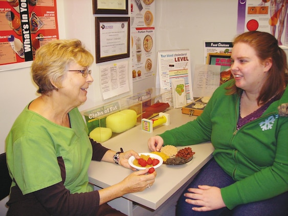 Patty Underdahl, left, health promotions coordinator, Naval Branch Health Clinic Albany, speaks to Victoria Herring, spouse and a program participant, about the proper portion sizes to eat during each meal, recently.