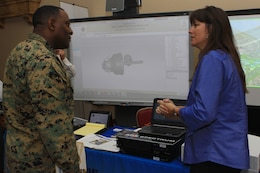 Master Gunnery Sgt. Antoine M. Brown, the communications chief for 1st Marine Logistics Group, and Janine Zaffino, the regional sales manager for CompView Audio-Video Systems, converse on the advantages of some of the world's latest technology during the semi-annual Technology Expo at the Pacific Views Event Center here Dec. 6.