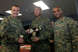 Brig. Gen. Vincent A. Coglianese, left, and Sgt. Maj. Derrick Christovale, right, pose with Staff Sgt. Jamal K. Blacknall here Dec. 6 after presenting the staff sergeant with a Navy Achievement Medal and a plaque for his service in various positions in the base's Single Marine Program. Blacknall serves as a radio technician with the 11th Marine Regiment here. Coglianese is the base commanding general and regional authority for five military installations in the Southwestern United States and Christovale is his senior enlisted advisor.