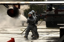 Firefighters extinguish an engine fire on the wing of a mobile aircraft fire trainer as part of a training scenario on Kadena Air Base, Japan, Dec. 4, 2012. As part of their training, the firefighters were tasked with putting out simulated exterior fires, followed by entering the aircraft and extinguishing interior fires to complete the training scenario. (U.S. Air Force photo/Airman 1st Class Hailey R. Davis)