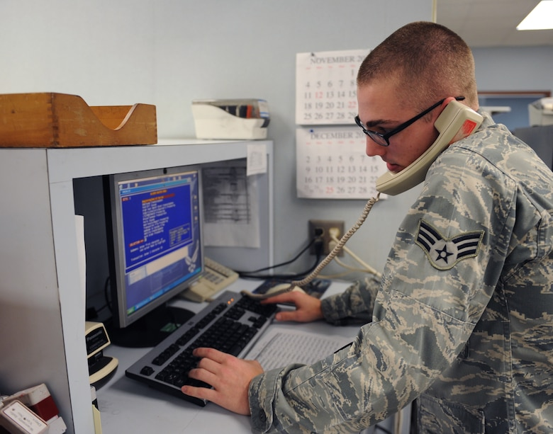Senior Airman Mitchal Anderson, 2nd Logistics Readiness Squadron Vehicle Management and Analysis journeyman, speaks to a customer while navigating the On-Line Vehicle Interactive Management System on Barksdale Air Force Base, La., Dec. 3. VMA schedules maintenance and inspections for every government-owned vehicle on base. They use OLVIMS to track the maintenance record of every GOV, and determine what services it needs. (U.S. Air Force photo/Airman 1st Class Benjamin Gonsier)
