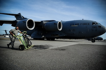 Staff Sgt. Norris Lewis, 437th Aircraft Maintenance Squadron crew chief, pushes a fire extinguisher into position as a C-17 Globemaster III arrives at the parking ramp, Dec. 5, 2012, at Joint Base Charleston - Air Base, S.C. After flight, maintenance crew chiefs ensure the aircraft remains operationally ready. (U.S. Air Force photo/Staff Sgt. Rasheen Douglas)