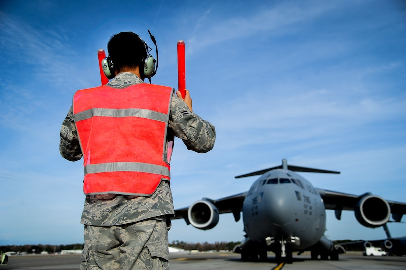 Airman 1st Class Justin Locsin, 437th Aircraft Maintenance Squadron crew chief, marshals a C-17 Globemaster III to its parking spot after landing Dec. 5, 2012, at Joint Base Charleston - Air Base, S.C. Maintainers are responsible for maintaining and repairing all parts of the aircraft. (U.S. Air Force photo/Staff Sgt. Rasheen Douglas)