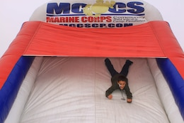 Gabriel M. Maldonado, 9, slides down the end of a children's obstacle course during the 2012 Trees for Troops event here Dec. 7.