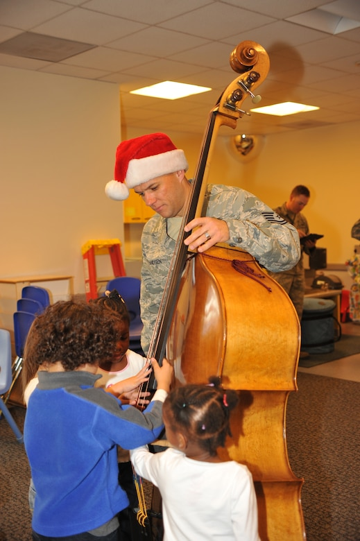 Air Force Tech. Sergeant Mark Frandsen, a musician with the Air Force Band of the Golden West demonstrates to children how to pluck the strings on an upright bass at the Child Development Center, Dec. 7.  The Band of the Golden West is stationed in the San Francisco Bay area at Travis Air Force Base, Calif. The only active duty Air Force band west of the Rockies, the band is comprised of 47 Airmen-musicians.   (Photo by Sarah Corrice)