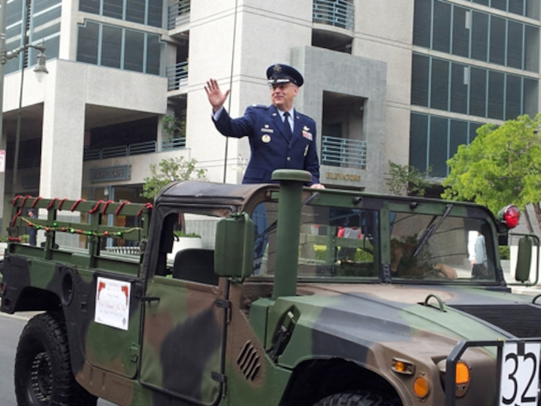 Colonel Sam McNiel, 61st Air Base Group commander, waves to the crowd during the San Pedro Holiday Parade, Dec. 2. The annual parade kicks off the holiday season in San Pedro. (Photo by Madlyn Washington)