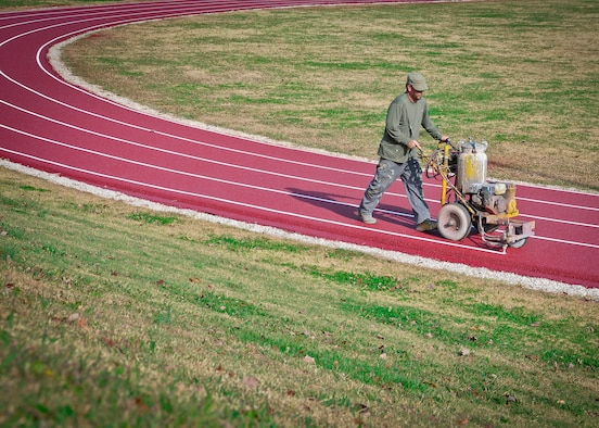 "Robb Haynes lays down the final stripe on the newly resurfaced running track at McGhee Tyson ANG Base, Tenn. Haynes walks at a fast pace as he paints the running stripes, averaging five minutes per lap. ""Once you get it laid out, the lines go down pretty quick,"" he said.  (U.S. Air Force Photo by 2nd Lt. Nathan Wallin)"