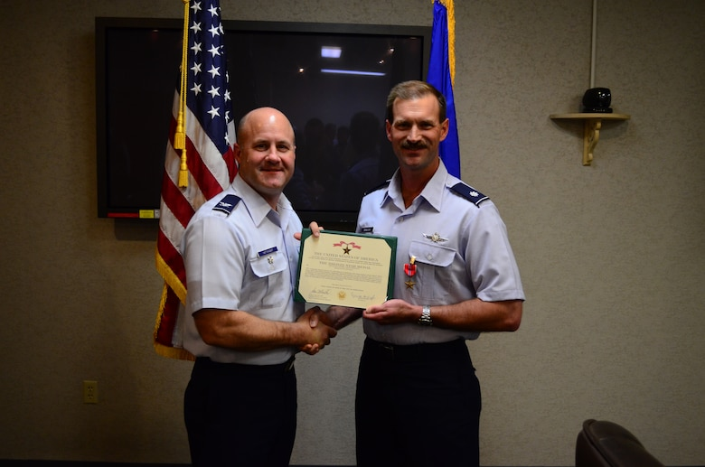 JOINT BASE SAN ANTONIO-LACKLAND, Texas -- Col. David Hathaway, 24th Air Force director of operations, presents the certificate for the Bronze Star Medal to Lt. Col. James Burleigh, 24th Air Force Operations director of current operations, during a ceremony here Sept. 24th. Burleigh was also awarded the U.S. Army Combat Action Badge for his actions while deployed to Afghanistan as the Expeditionary Cyber Support Element - Afghanistan deputy officer in charge and computer network operations planner. He was the mission commander for more than 5,000 cyber operations. (U.S. Air Force photo by William Parks)