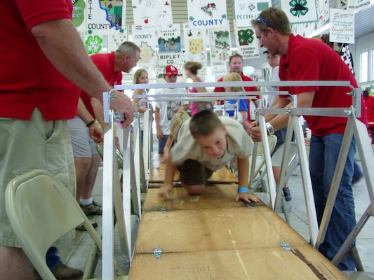 Volunteers assist as children raise a small, aluminum and wood bridge replica at the Missouri State Fair. This was part of an effort to educate the kids on civil engineering. Photo provided.