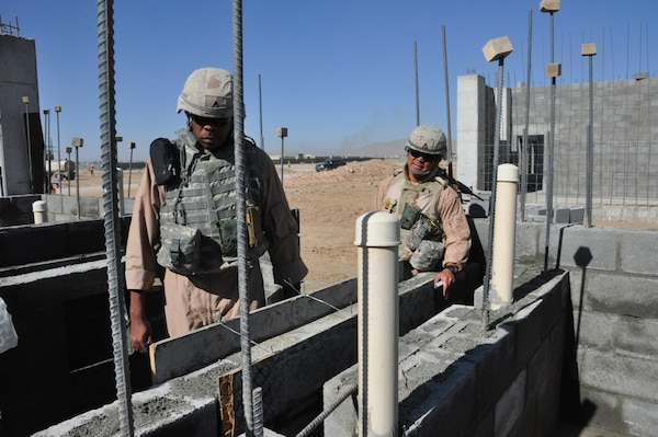 Ira Dorsett, a structural engineer, (left) and Benny Apuya, (right) a quality assurance and construction representative, both with the Afghanistan Engineer District-South inspect the masonry block work for a concrete sink at the Kandahar Regional Military Training Center construction site Nov. 18. Both visit the site several times a week to make sure construction complies with plans and specifications as well as International Building Code standards.