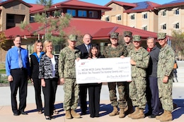 Caroline Winn, center, and Brig. Gen. Vincent A. Coglianese, center-right, pose with other participants of the Savings by Design program, which assists in lowering the long-term energy costs of building projects.  Winn, the vice president of San Diego Gas and Electric, presented a check for $1,002,570.42  to Coglianese, the base commanding general and regional authority for five Marine Corps installations in the Southwestern United States Dec. 10.