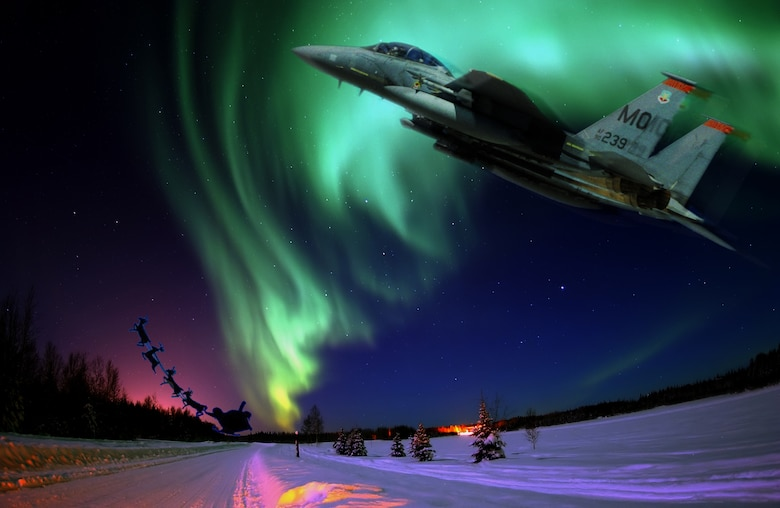 MOUNTAIN HOME AIR FORCE BASE, Idaho – An F-15E Strike Eagle rushes to assist Santa Claus and serves as his wingman as he delivers presents around the world. Flying a 'sleigh' powered by two Pratt and Whitney engines and capable of flying at speeds in excess of 1,800 mph, Maj. Kristin Wehle, 366th Fighter Wing F-15E pilot, believes she and other Air Combat Command pilots could be Santa's perfect wingman, she said. (U.S. Air Force photo illustration/Master Sgt. Kevin Wallace/RELEASED) -Original Aurora Borealis photo by Senior Airman Joshua Strang