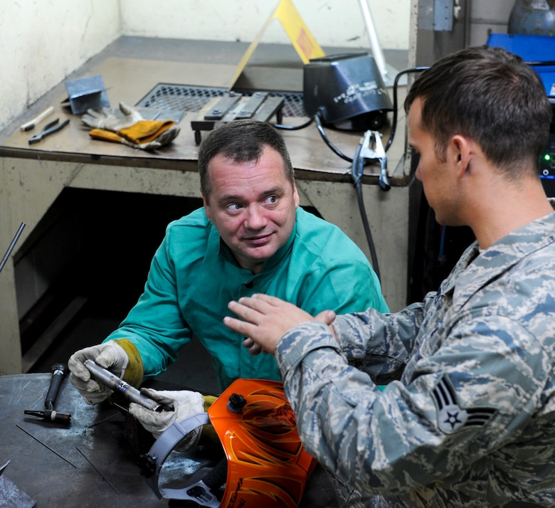 U.S. Air Force Senior Airman Christopher Zampese, 18th Equipment Maintenance Squadron aircraft metals technology technician, presents Col. Brian McDaniel, 18th Wing vice commander, with an example of a well done tungsten-electrode inert gas welding technique on Kadena Air Base, Japan, Dec. 6, 2012. TIG is a slower welding technique, but the quality of weld tends to be cosmetically better because there is no weld splatter and it has a clean finish, according to Senior Master Sgt. Roger Starcher, 18th EMS Fabrication Flight superintendant. (U.S. Air Force photo/Airman 1st Class Justin Veazie)