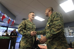 Brig. Gen. Vincent A. Coglianese, left, congratulates Staff Sgt. Jamal K. Blacknall here Dec. 6 after presenting the staff sergeant with a Navy Achievement Medal and a plaque for his service in various positions in the base's Single Marine Program. Blacknall serves as a radio technician with the 11th Marine Regiment here. Coglianese is the base commanding general and regional authority for five military installations in the Southwestern United States.