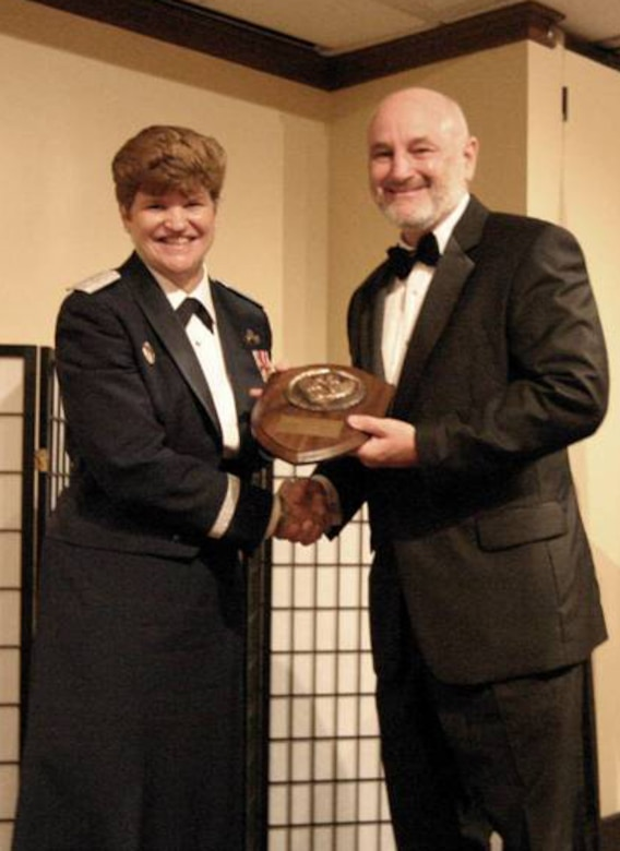 Dave Madden, MILSATCOM director receives a plaque from Gen. Janet Wolfenbarger, Air Force Material Command commander, upon his induction into the Space Operations Hall of Fame, Nov. 3. (Photo provided by the San Jose Chapter of the AFA)
