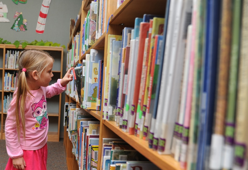Sophia Francis, 5, daughter of Amanda and Maj. Mark Francis, 81st Surgical Operations Squadron, searches through a shelf of books in the children's room at the McBride Library Dec. 6, 2012, Keesler Air Force Base, Miss.  (U.S. Air Force photo by Kemberly Groue)
