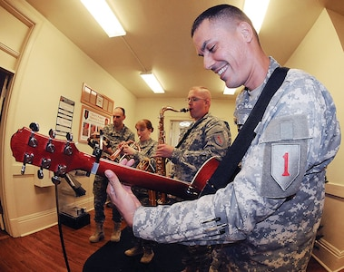 Four members of the 1st Infantry Division Band entertain employees Dec. 5 at the Fort Riley Garrison Public Affairs Office on Main Post.  From left to right are: Staff Sgt. Travis Guidry on percussion; Staff Sgt. Rebecca Goncalves on the flugel horn; Sgt. James Shank on the sax; and Staff Sgt. Andre Goncalves on guitar.  The jazz combo quartet was one of four different ensemble groups – which also included a brass ensemble, a quintet and four members of the 1st Inf. Div.'s rock band, Gun Powder and Lead – performing holiday carols for offices and businesses at Fort Riley and in the Junction City and Manhattan communities.  Photo by: Dena O'Dell, POST.