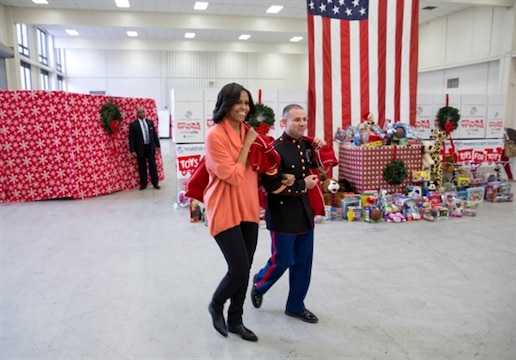 Staff Sgt. Joel Vazquez escorts First Lady Michelle Obama as she arrives with a sack full of toys at the Toys for Tots Distribution Center at Joint Base Anacostia-Bolling in Washington, D.C., Dec. 11, 2012.