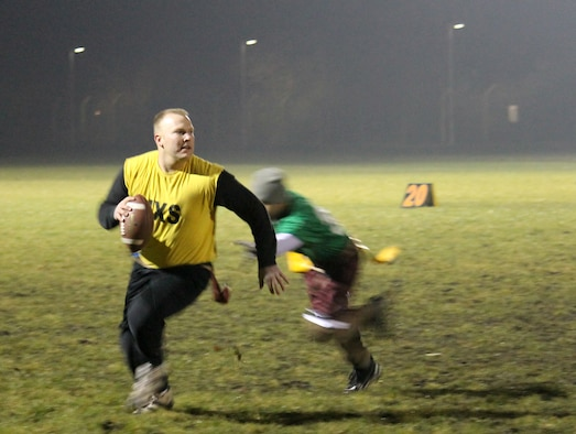 Staff Sgt. Brian Szarek, 100th Maintenance Group team quarterback, avoids a tackle during the RAF Mildenhall flag football championship game Dec. 12, 2012, at RAF Mildenhall, England. Maintenance defeated the 100th Communications Squadron/Force Support Squadron team by a final score of 14-12. (U.S. Air Force photo by Capt. Jason Smith/Released)