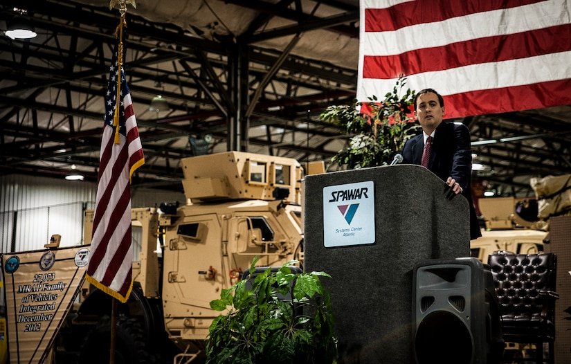 Christopher Miller, Space and Naval Warfare Systems Center Atlantic executive director, speaks to invited guests and workers who helped integrate the mine-resistant, ambush-protected vehicles at a ceremony held to commemorate the rapid acquisition, integration of electronics and delivery of more than 27,000 MRAP vehicles sent to Iraq and Afghanistan, Dec. 10, 2012, from the SPAWAR integration facility on Joint Base Charleston – Weapons Station, S.C. The team at SPAWAR initially integrated five vehicles a day, but when demand for the vehicles rose, the team stepped production up to integrating 50 vehicles a day. The team even reached the lofty goal of integrating 75 MRAPSs in one day. (U.S. Air Force photo/ Senior Airman Dennis Sloan)