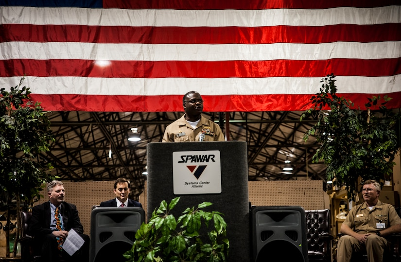 Navy Capt. Mark Glover, Space and Naval Warfare Systems Center Atlantic commanding officer, welcomes attendees to a ceremony held to commemorate the rapid acquisition, integration of electronics and delivery of more than 27,000 MRAP vehicles sent to Iraq and Afghanistan, Dec. 10, 2012, from the SPAWAR integration facility on Joint Base Charleston – Weapons Station, S.C. The team at SPAWAR initially integrated five vehicles a day, but when demand for the vehicles rose, the team stepped production up to integrating 50 vehicles a day. The team even reached the lofty goal of integrating 75 MRAPSs in one day. (U.S. Air Force photo/ Senior Airman Dennis Sloan)