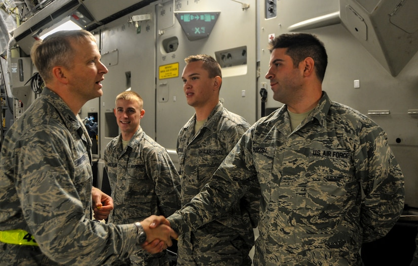 Col. Darren Hartford, 437th Airlift Wing commander, shakes hands with Airman Zachary Buzzell, 373rd Training Squadron crew chief student, during an incentive flight, Dec. 6, 2012, aboard a C-17 Globemaster III at Joint Base Charleston – Air Base.  More than 50 quarterly award winners attended the incentive flight onboard two C-17s which were conducting air drop training missions at Joint Base Charleston's – North Auxiliary Air Field. (U.S. Air Force photo/ Airman 1st Class Jared Trimarchi)